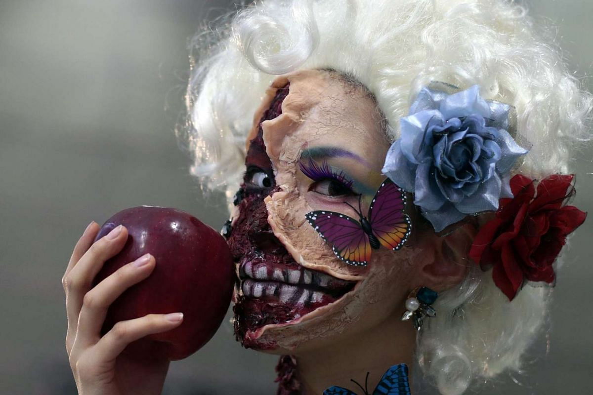 A participant in costume holding an apple poses for a picture after the Kawasaki Halloween event in Kawasaki city on Oct 30, 2016.