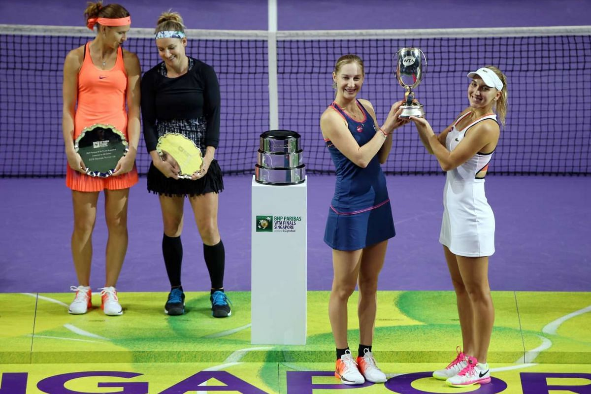 Ekaterina Makarova (second from right) and Elena Vesnina celebrate with their trophy after winning the WTA Women's Doubles final on Oct 30, 2016, as Lucie Safarova and Bethanie Mattek-Sands look on.