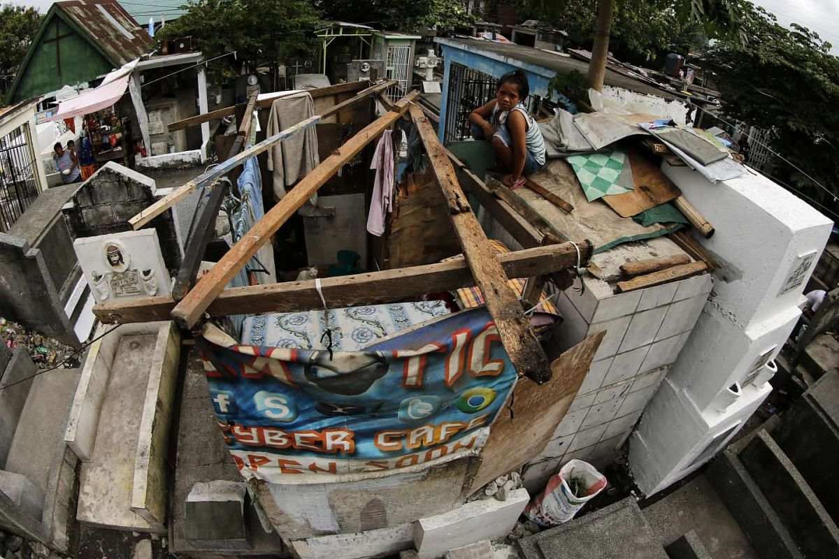 A Filipino informal settler rests on a shanty built on top of graves ahead of All Saints Day at a public cemetery in Pasay city, Philippines, on Oct 31, 2016.