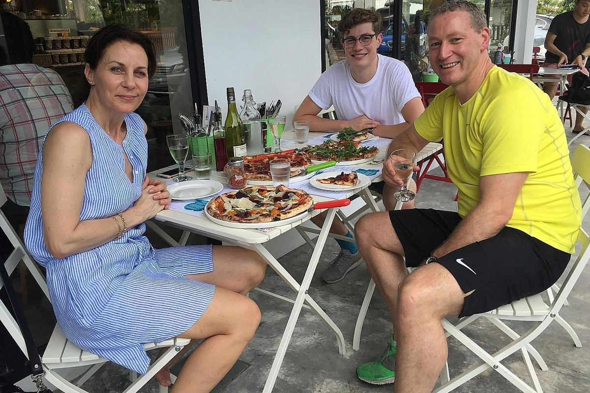My life so far: Mr Dean Brettschneider at the Rangiora Bakery in New Zealand where he apprenticed as a teenager; and with wife Vibeke and son Jason at Plank pizzeria in Opera Estate this year (above).