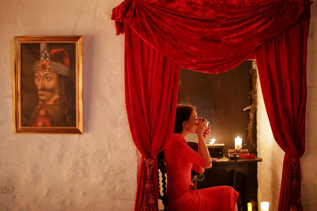 Tami Varma retouches her make-up next to a portrait of Vlad the Impaler, medieval prince of Wallachia, before posing for media representatives in one of the rooms of Bran Castle in Brasov county, Romania, on Oct 31, 2016.