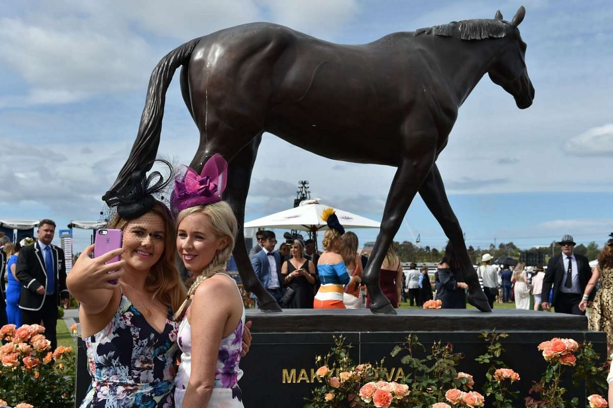 Racegoers pose for a selfie in front of the Makybe Diva statue at Flemington Racecourse on Melbourne Cup day in Melbourne on Nov 1, 2016.
