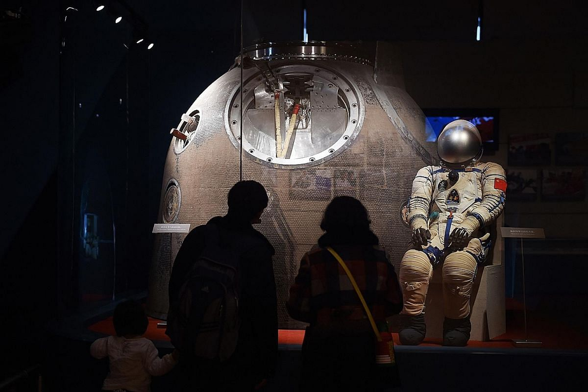 Top: A poster of Chinese astronauts at the Jiuquan Satellite Launch Centre. Above: A family in Beijing views the spacesuit and re-entry capsule used by China's first astronaut Yang Liwei.