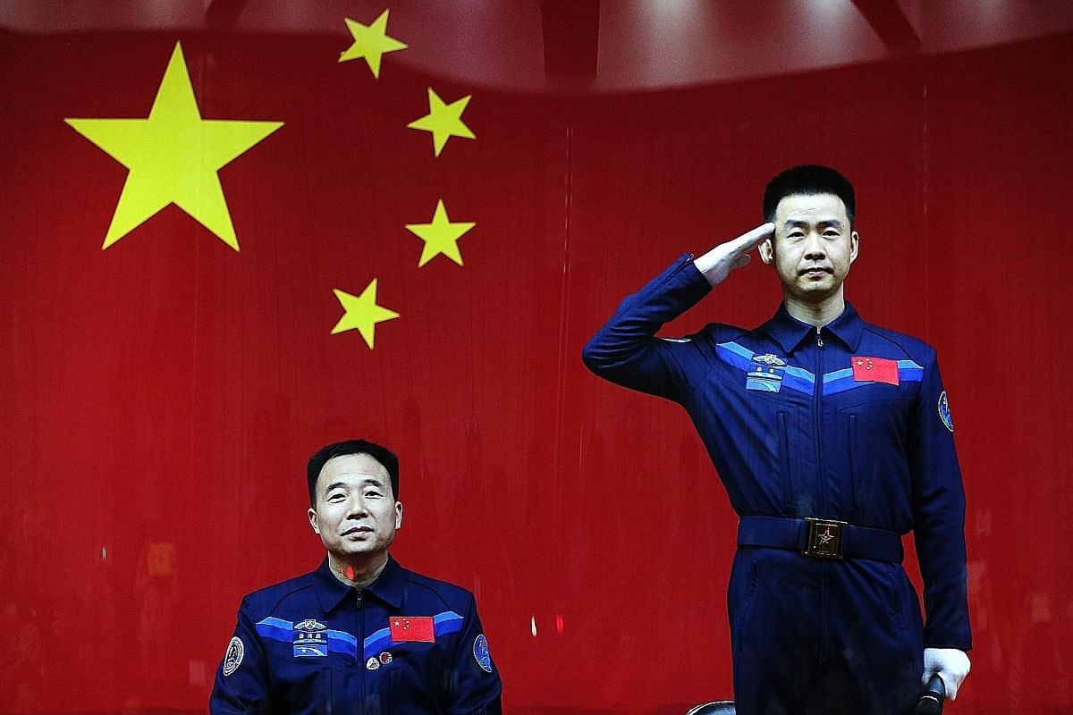 The Shenzhou-11 spacecraft on its carrier rocket, the Long March-2F. The rocket took off on Oct 17. Top: Chinese astronaut Chen Dong saluting as fellow astronaut Jing Haipeng looks on during a media session at the Jiuquan Satellite Launch Centre in G