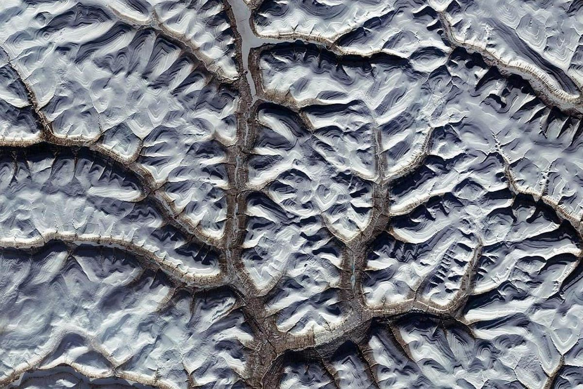 An image captured by the Copernicus Sentinel-2A satellite over the snowy landscape of the Putorana Plateau in northern Central Siberia, Russia.