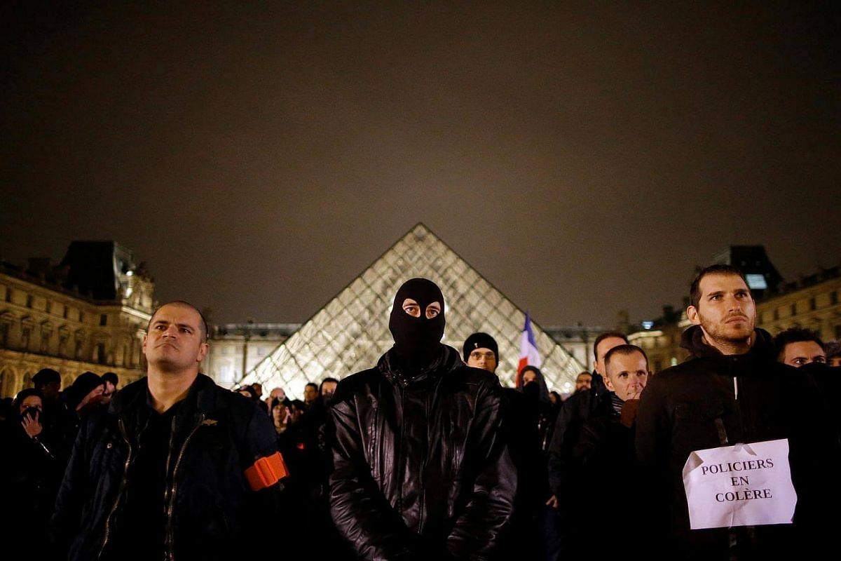 Police officers stand in front of the Louvre Pyramid designed by Chinese-born US Architect Ieoh Ming Pei during a protest against anti-police violence in Paris, France, on Nov 1, 2016.