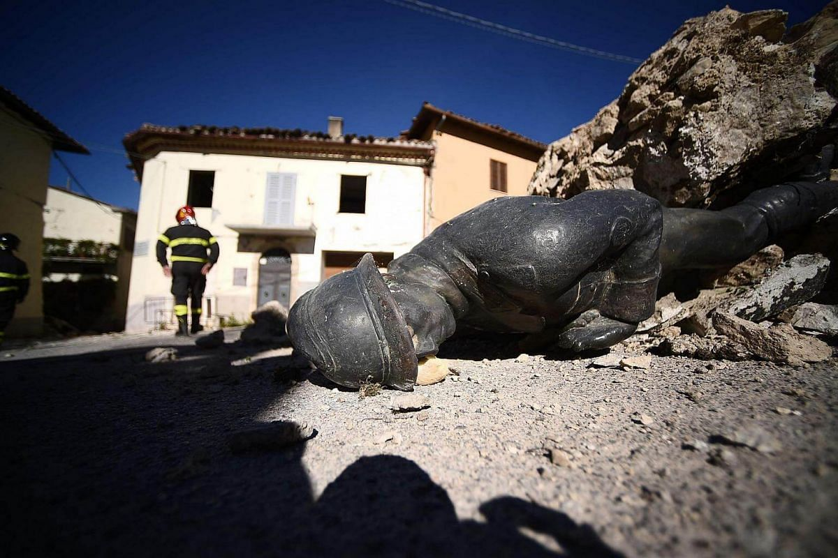 The statue of a memorial lies on the ground in the village of San Pellegrino near Norcia, on Nov 1, 2016, two days after a 6.5 magnitude earthquake hit central Italy.