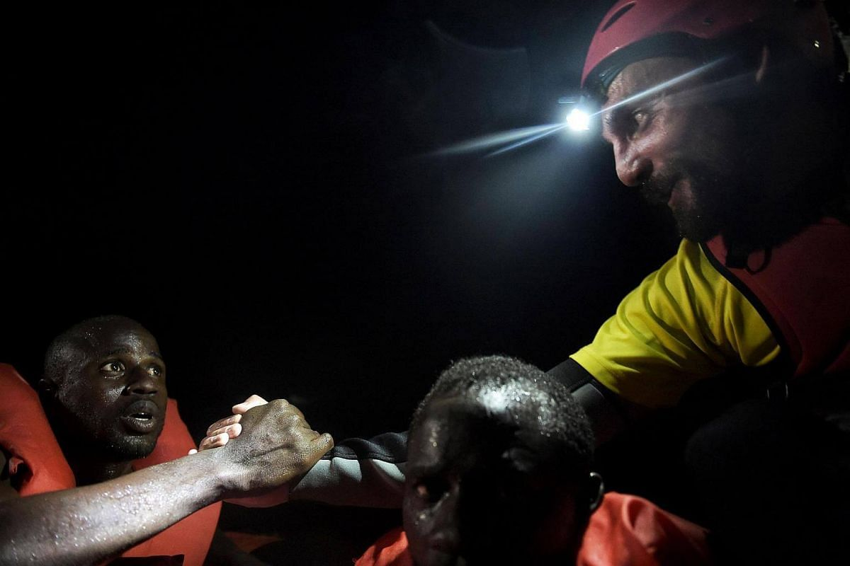 A migrant thanks Marcos Chercoles Ruiz, a member of Spanish humanitarian NGO Proactiva Open Arms, during a night rescue operation off the coast of Libya on Oct 12, 2016.