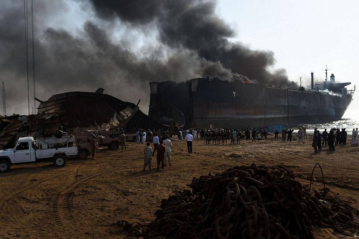 Pakistani bystanders gather around the wreckage of a burning ship after a gas cylinder explosion at the Gadani shipbreaking yard, some 50 kilometres west of Karachi on Nov 1, 2016.