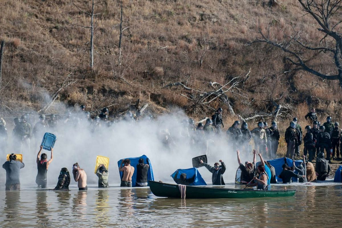 Police use pepper spray against people standing in the water of a river during a protest against the building of a pipeline on the Standing Rock Indian Reservation near Cannonball, North Dakota, US, on Nov 2, 2016.