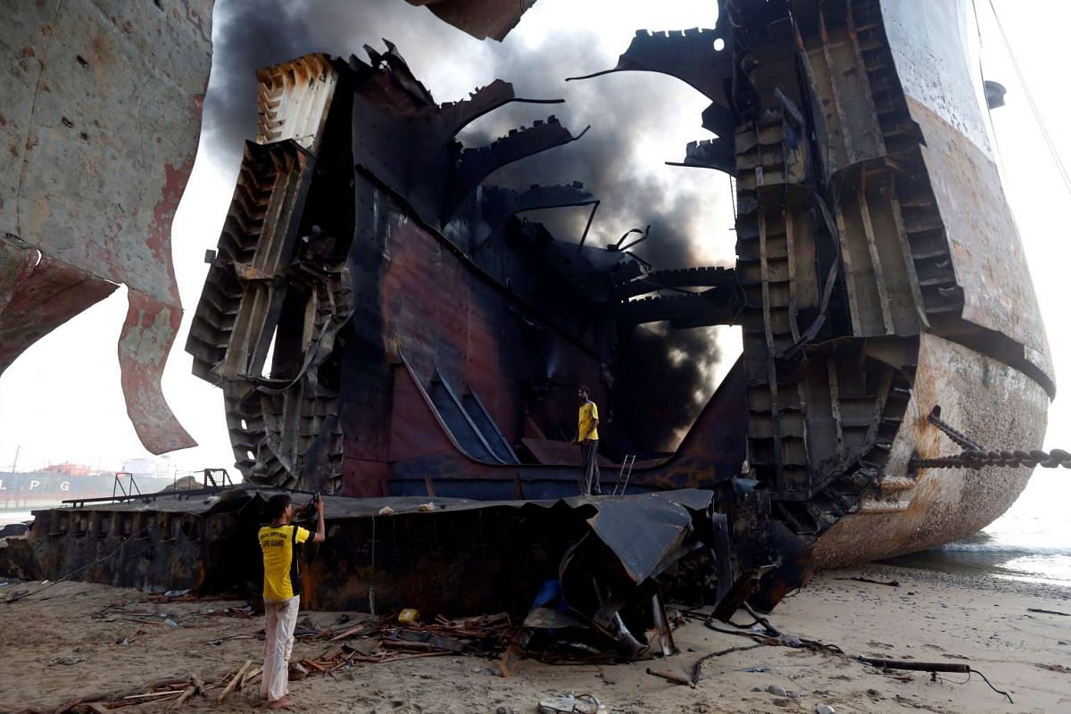 A man takes photo of his colleague with a mobile phone on the burning oil tanker at the ship-breaking yard in Gaddani, Pakistan, on Nov 2, 2016.