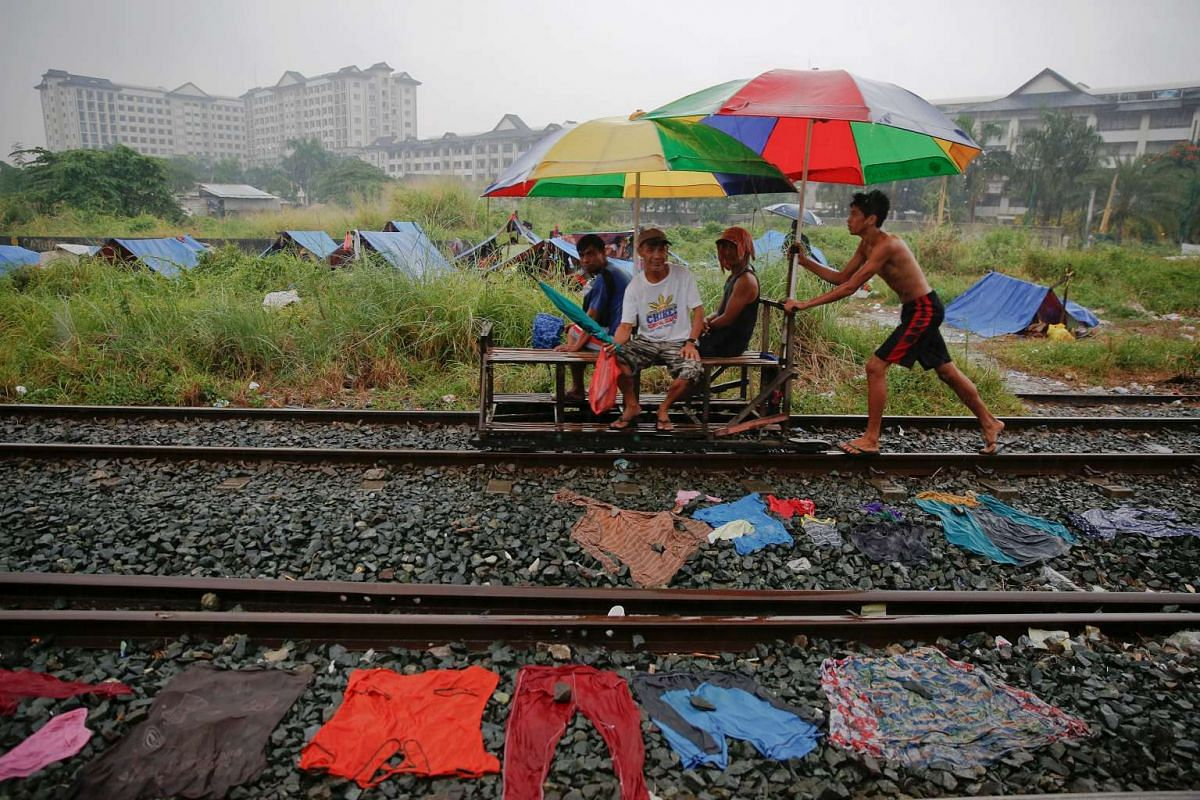 A man pushes passengers on a makeshift trolley in an area where, according to local residents, several people have been killed in police operations since the beginning of country's war on drugs, in Manila, Philippines on Nov 2, 2016.