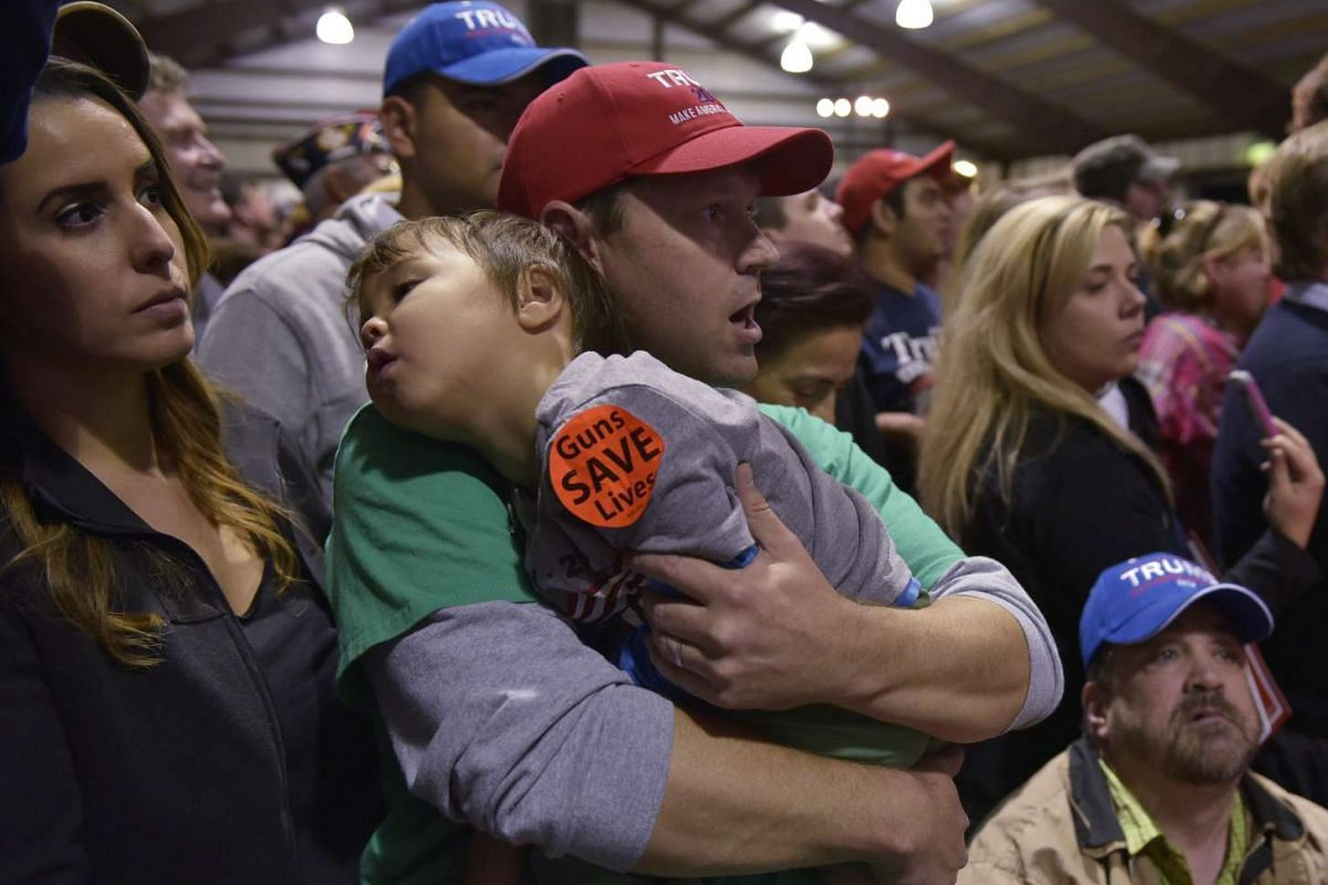 A supporter holds a child as Republican presidential nominee Donald Trump addresses a campaign rally at the Loudoun Fairgrounds in Leesburg, Virginia on Nov 7, 2016.