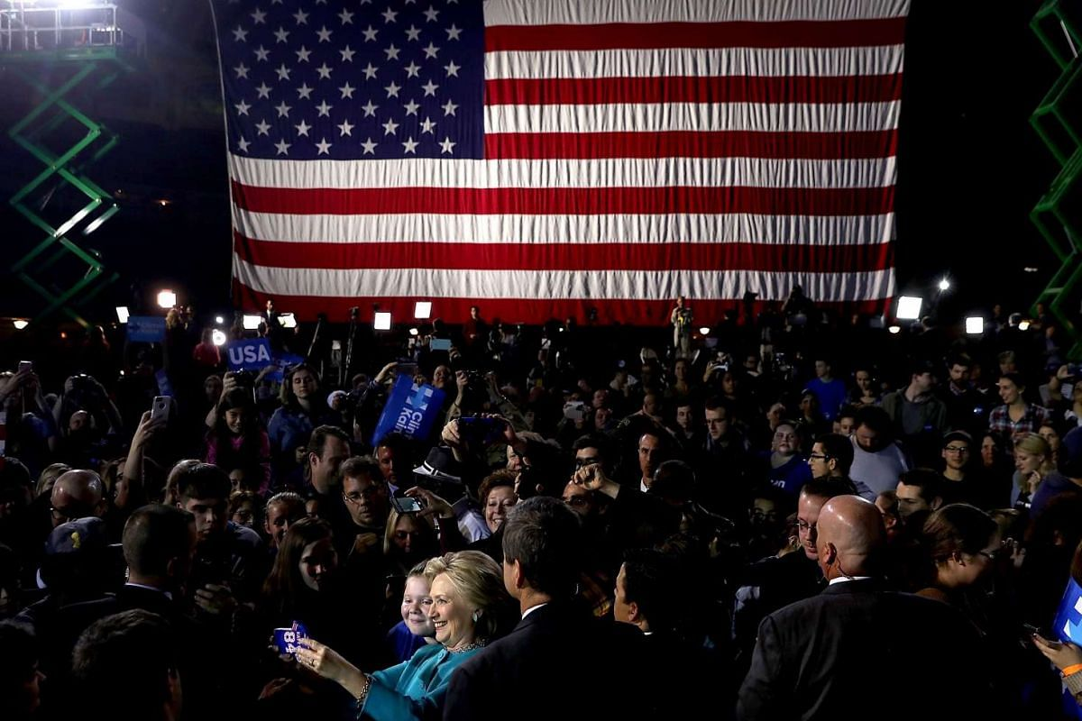 Democratic presidential nominee former Secretary of State Hillary Clinton takes a selfie with a supporter during a campaign rally at the Cleveland Public Auditorium on Nov 6, 2016.