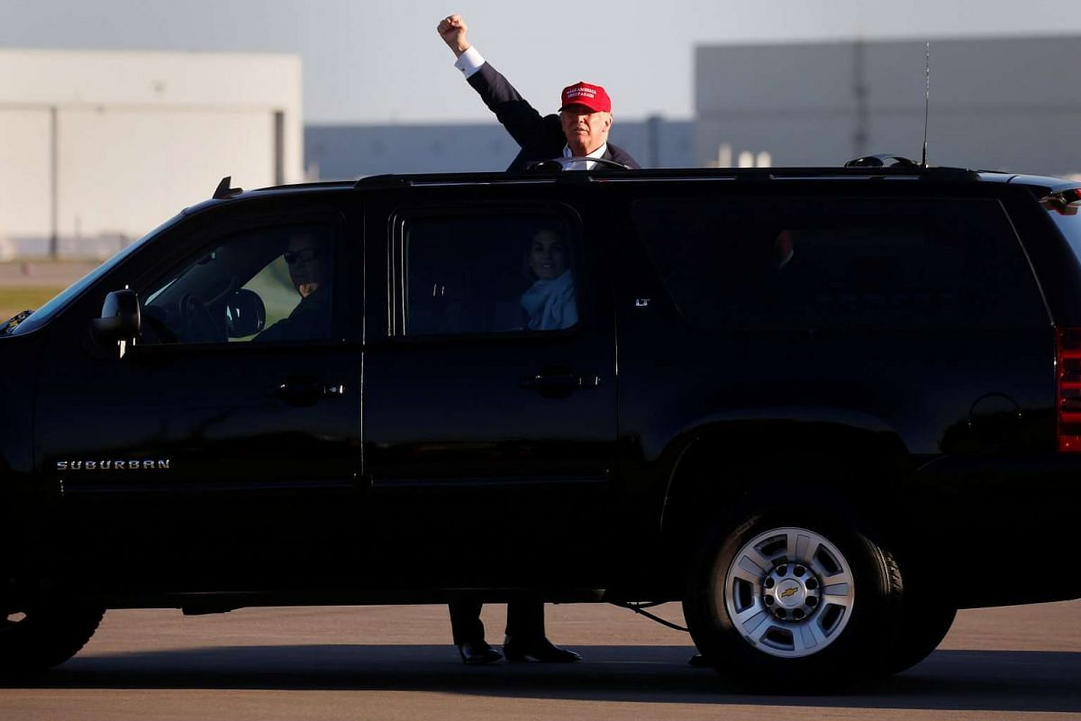 Republican presidential nominee Donald Trump stands on the running board of an SUV and waves at an overflow crowd at a campaign rally in Minneapolis on Nov 6, 2016.