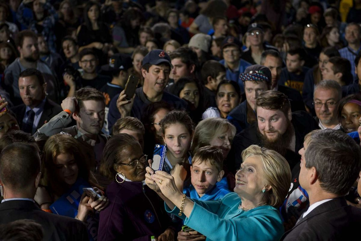 Democratic presidential nominee Hillary Clinton takes selfies with supporters after speaking a rally at the Cleveland Public Auditorium on Nov 6, 2016.