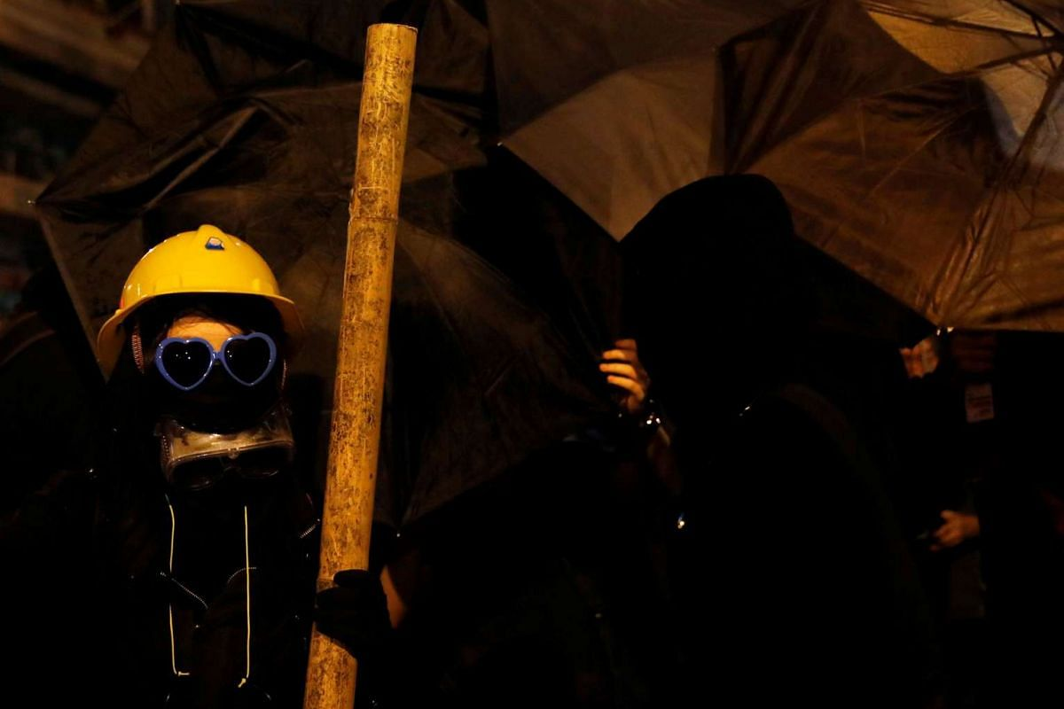 A masked demonstrator holds a bamboo rod during a confrontation with the police as they protest against what they call Beijing's interference over local politics and the rule of law in Hong Kong on Nov 7, 2016.