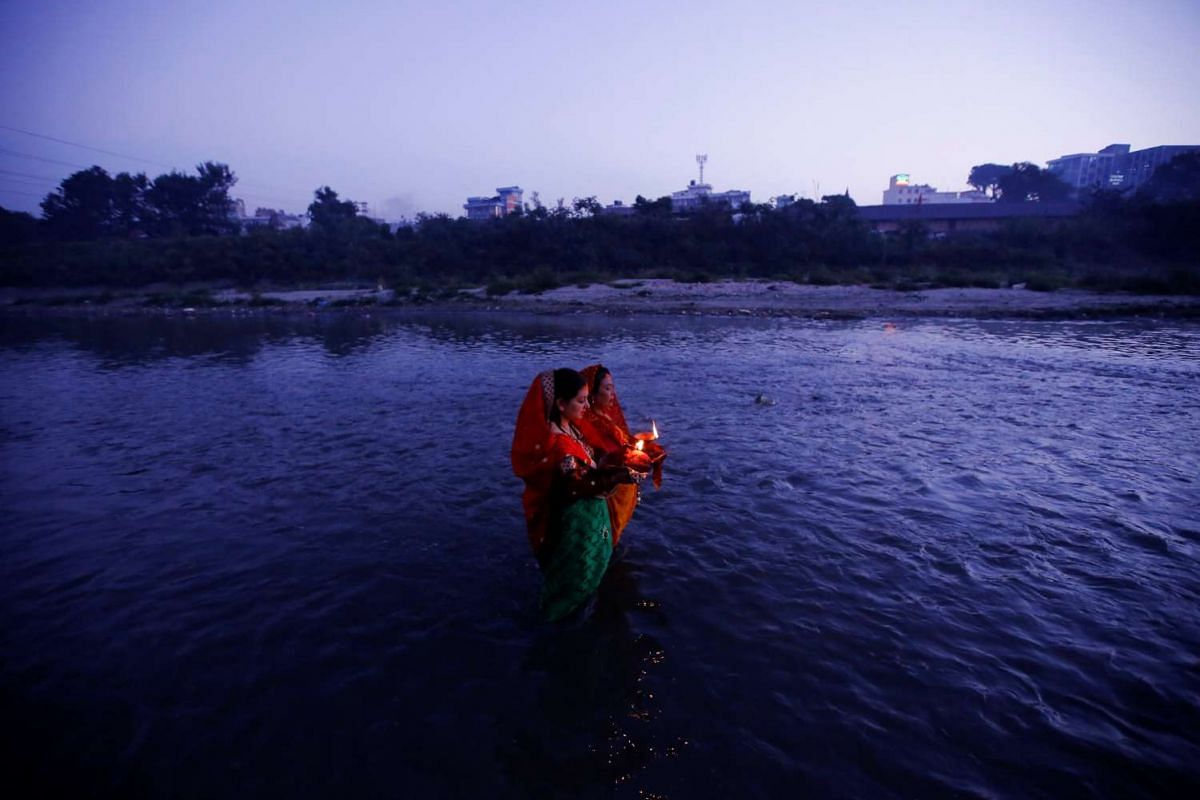 """Devotees offer prayers to the rising sun during the """"Chhat"""" festival at Bagmati River in Kathmandu, Nepal on Nov 7, 2016."""
