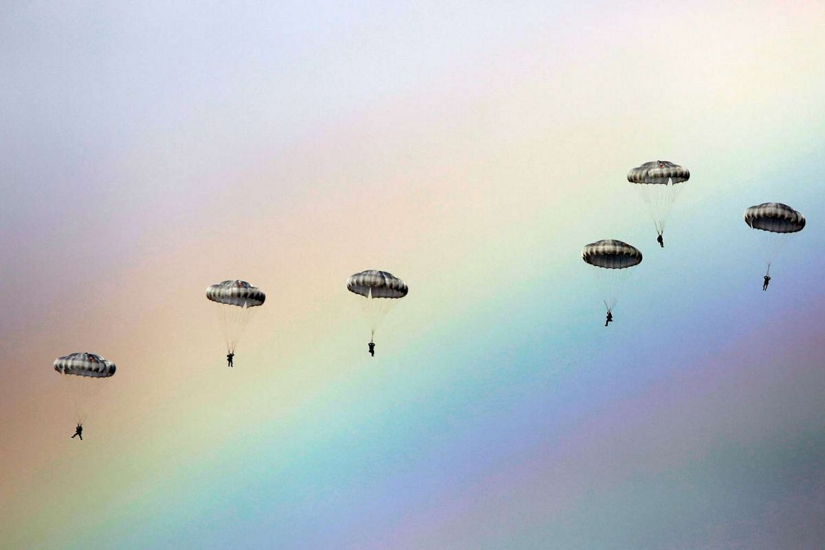"""Russian paratroopers jump as a rainbow appears in the sky during the joint Russian, Belarusian and Serbian military exercise called """"The Slavic Brotherhood"""" at the military ground at Kovin, near Belgrade, on Nov 7, 2016."""