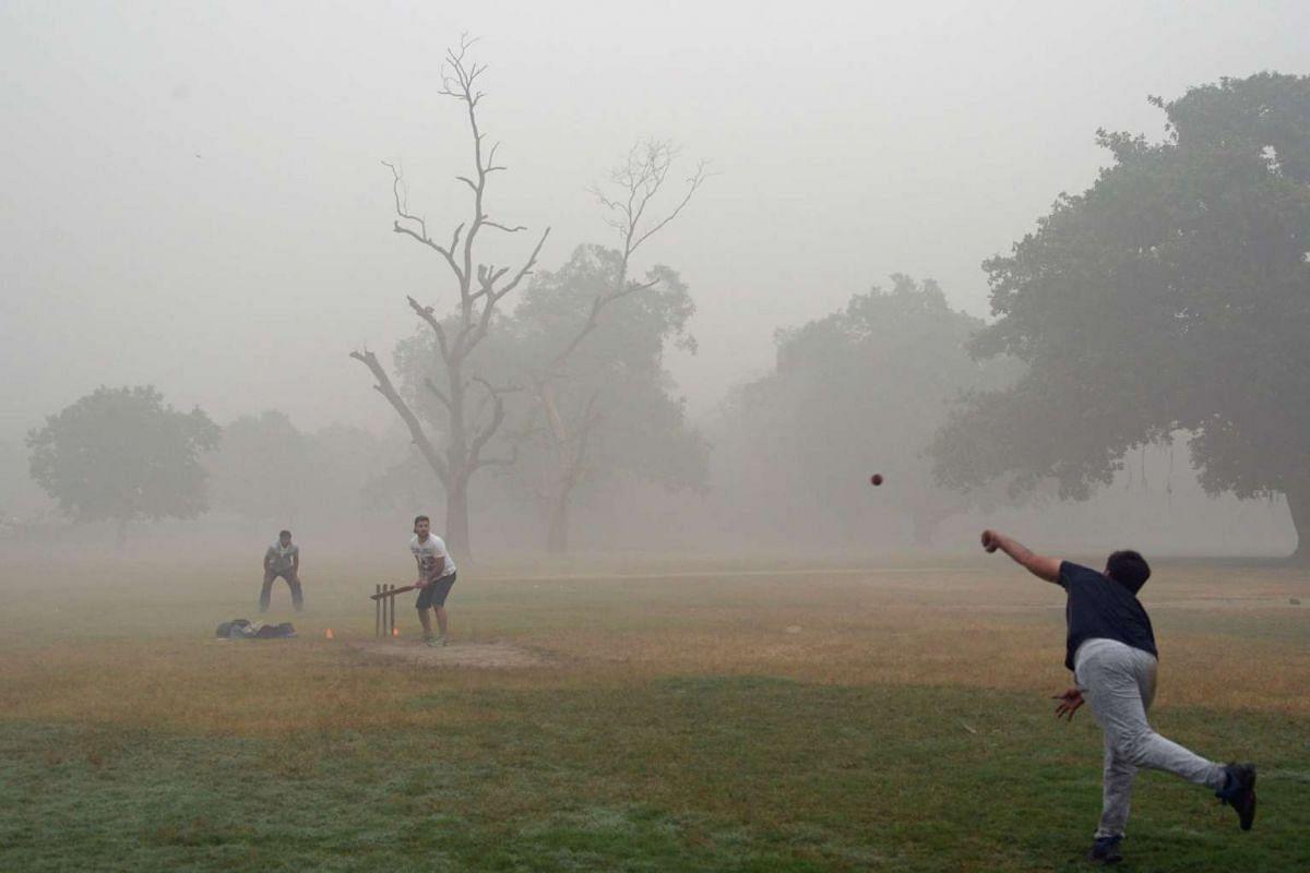 Indian men play cricket amid heavy smog in New Delhi, on Nov 6, 2016.