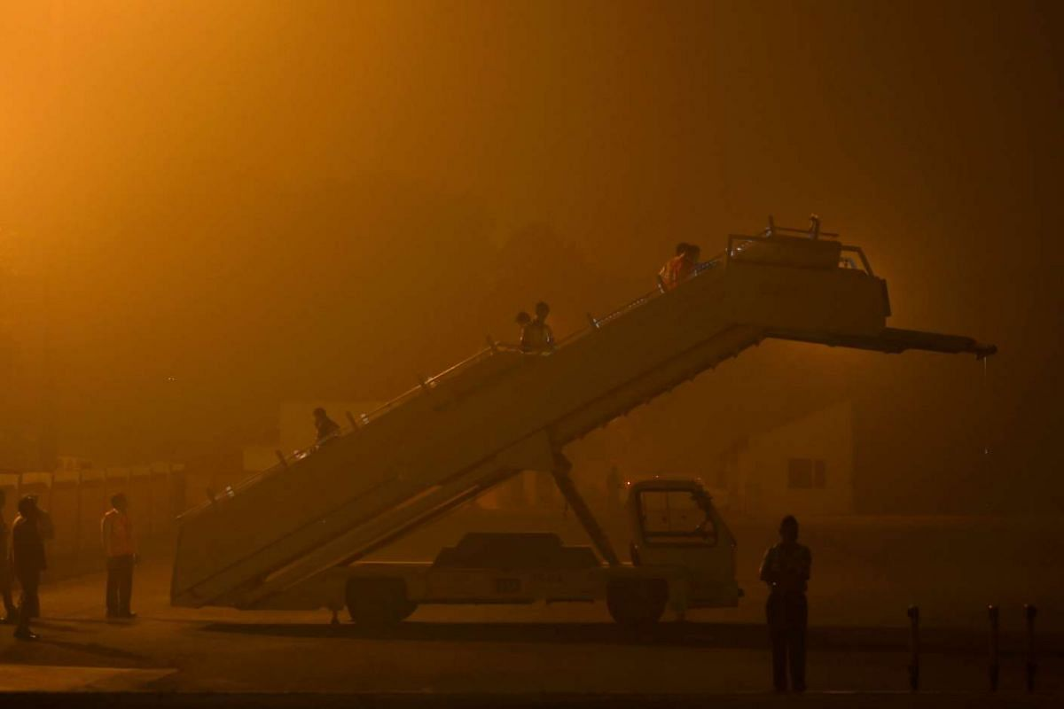 Indian groundstaff prepare a stairway for the arrival of an aircraft carrying Britain's Prime Minister Theresa May on a runway at a smog covered Palam Technical Airport in New Delhi, on Nov 6, 2016.