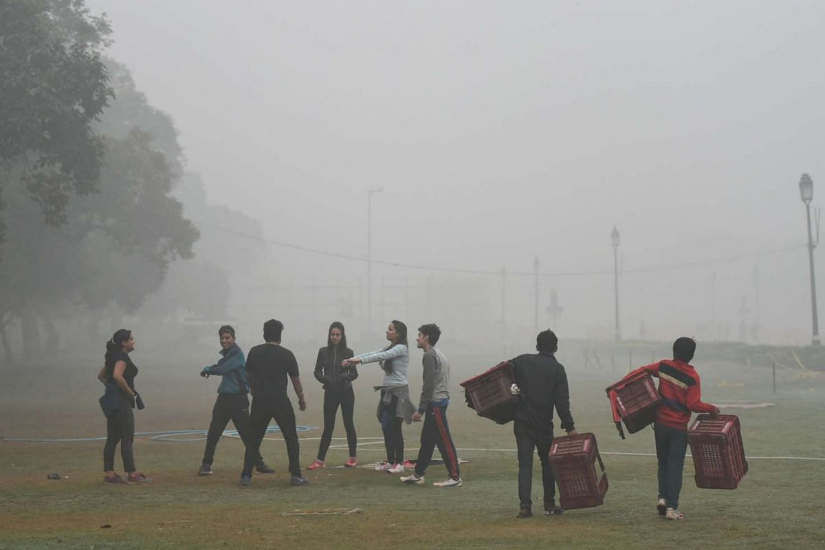 Young people do exercise as vendors carry plastic baskets in a park as heavy smog covers New Delhi, on Nov 7, 2016.