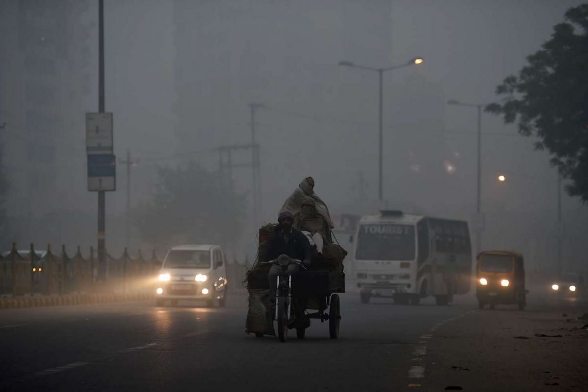Indian commuters journey along a main road as smog envelops in New Delhi, on Nov 7, 2016.