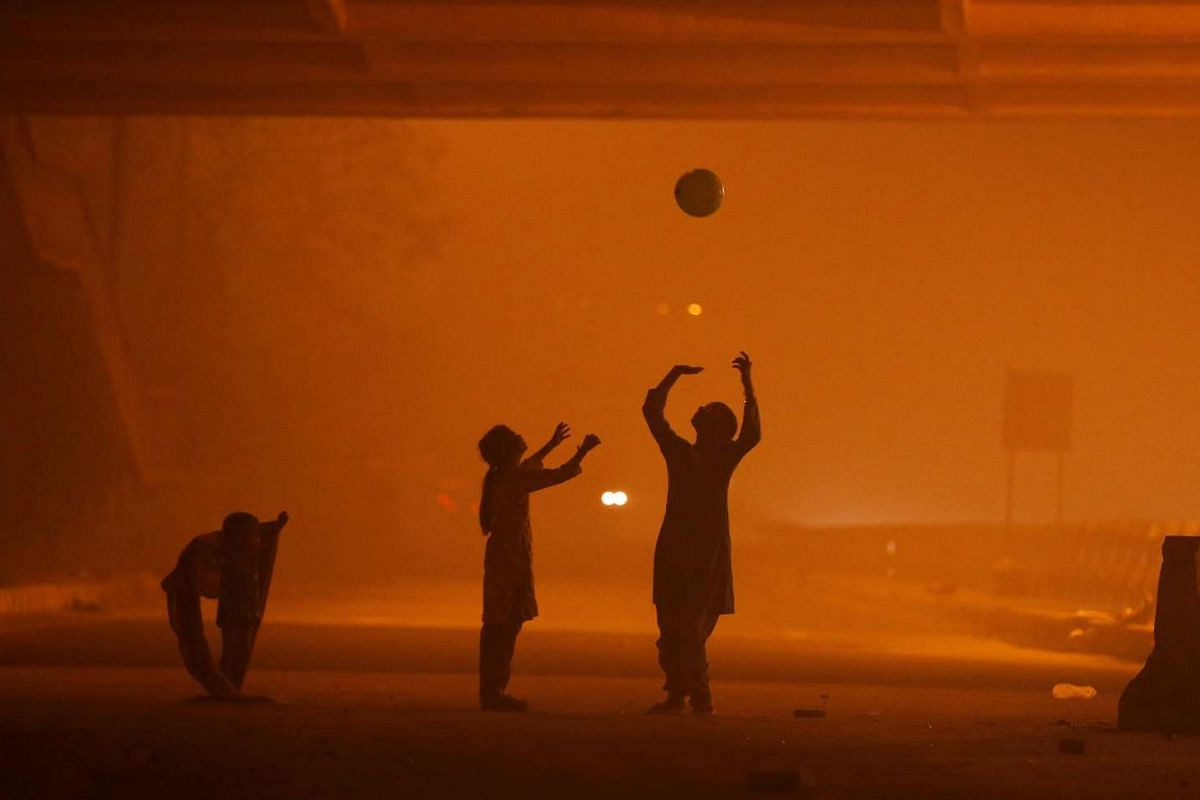 Girls play with a balloon under a flyover amidst the heavy smog in New Delhi, on Nov 6, 2016.