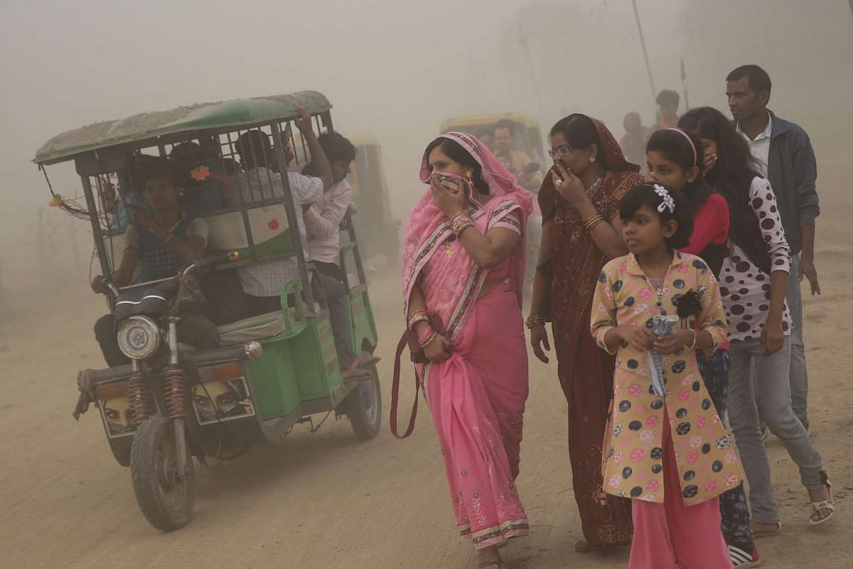 Indian pedestrians have their faces covered as they walk in heavy dust and smog in New Delhi, on Nov 6, 2016.