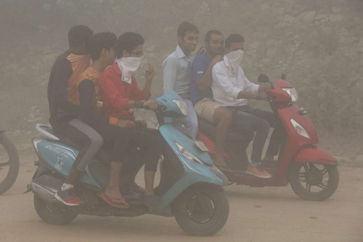 Indian men ride their motorbikes in heavy dust and smog in New Delhi, on Nov 6, 2016.