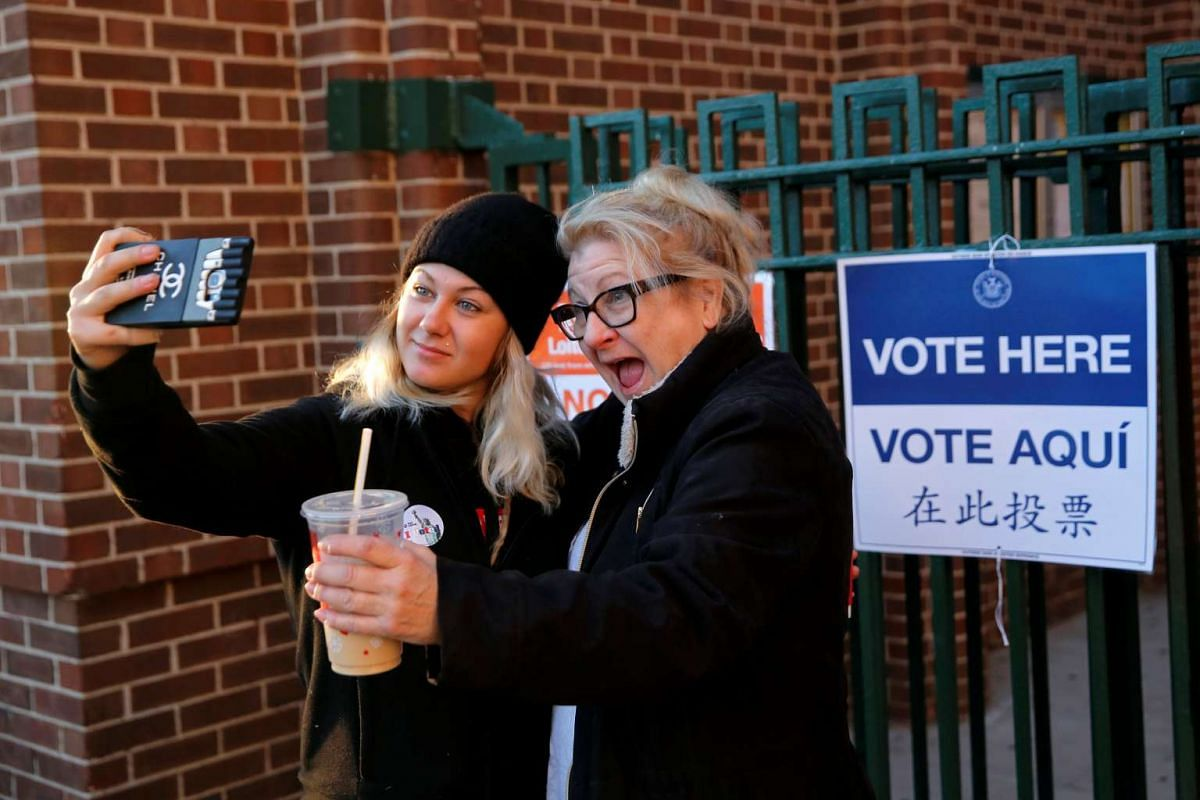 First time voter Kaeli Askea poses for a selfie with her mother Erin Collins-Askea after voting at the James Weldon Johnson school in the East Harlem neighbourhood of Manhattan on Nov 8, 2016.