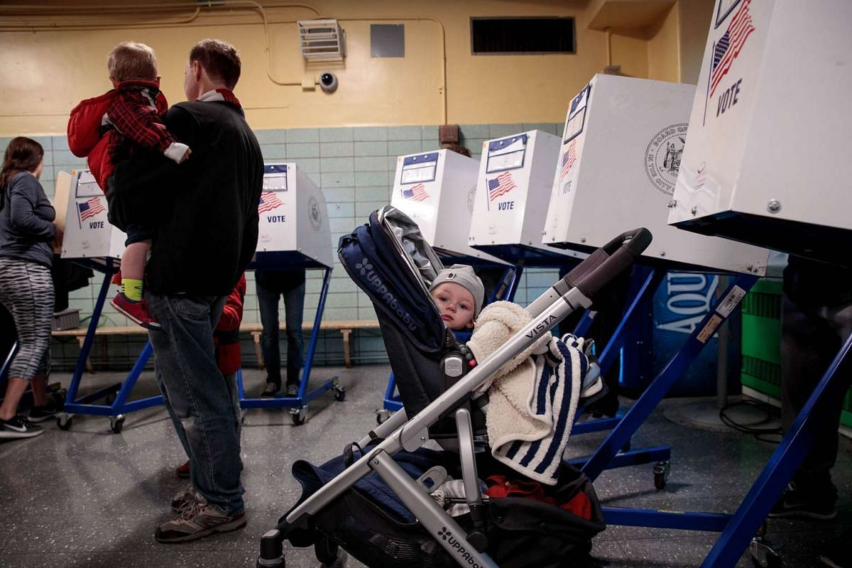 A baby waits as people vote at a polling site at Public School 261, Nov 8, 2016 in New York City.
