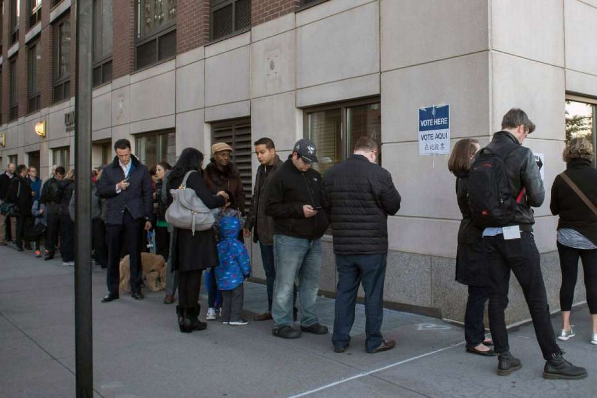 People stand in line outside a polling station located at Trump Place, Nov 8, 2016 in New York.
