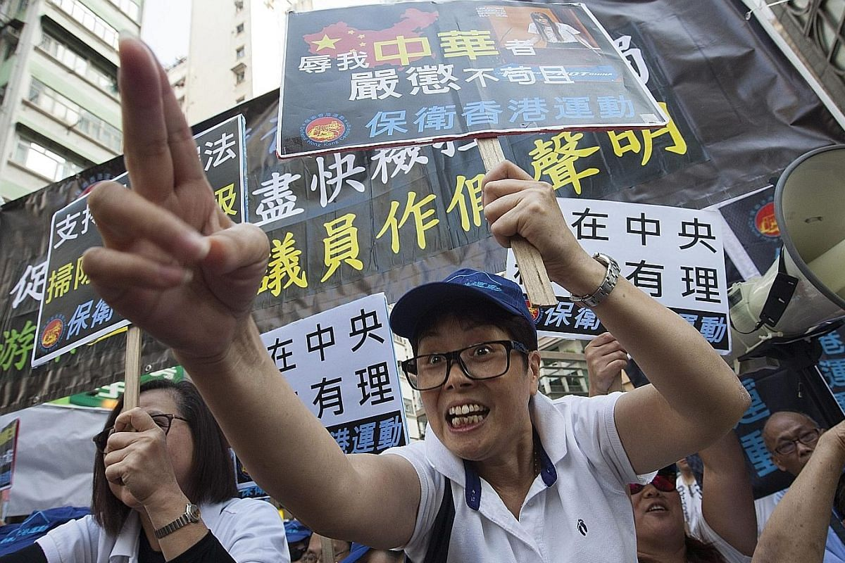 From left: No gas mask? Try cling wrap. A demonstrator protecting himself from pepper spray by wrapping his face in plastic; Pro-China supporters shouting abuse at pro-independence protesters on Sunday afternoon; and a protester in tears after being