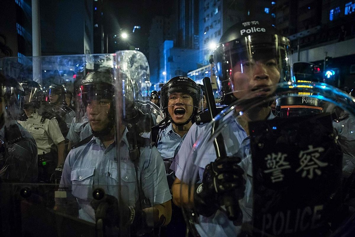 A police officer giving orders during Sunday's protest. Armed with shields and batons, a special force dispersed the thinning crowd at close to 1am yesterday. Four people were arrested and two police officers were injured during the clashes.