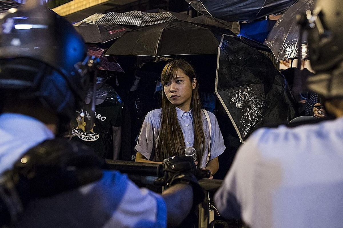 Top: Youngspiration's Mr Leung at a protest on Sunday against China's interpretation of Hong Kong's Basic Law. Above: Ms Yau (centre) at a protest near the Liaison Office of the Central People's Government in Hong Kong on Sunday.