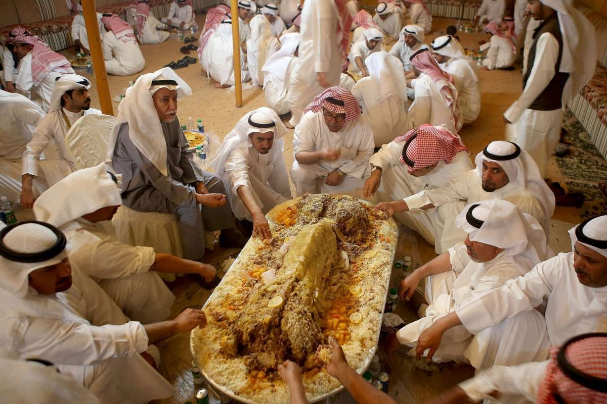 Kuwaitis eat a traditional Kuwaiti feast made from camel meat during an election campaign meeting for Kuwaiti candidate Al-Humaidi al-Subaei, for the upcoming parliamentary election, in Kuwait City on Nov 8, 2016.