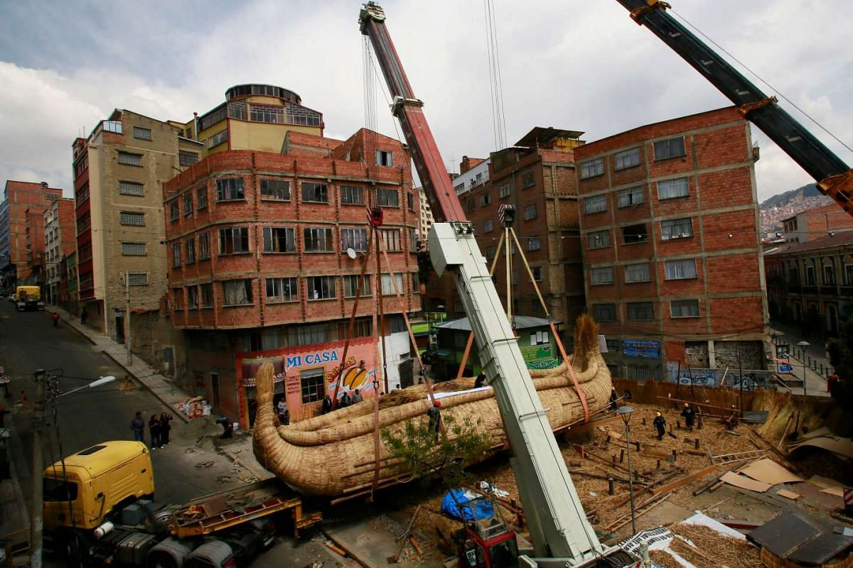"""Cranes place """"Viracocha III"""", a boat made only from totora reeds, on a trailer truck during preparations for the boat to cross the Pacific Ocean, from Chile to Australia on an expected six-month journey, in La Paz, Bolivia on Nov 8, 2016."""