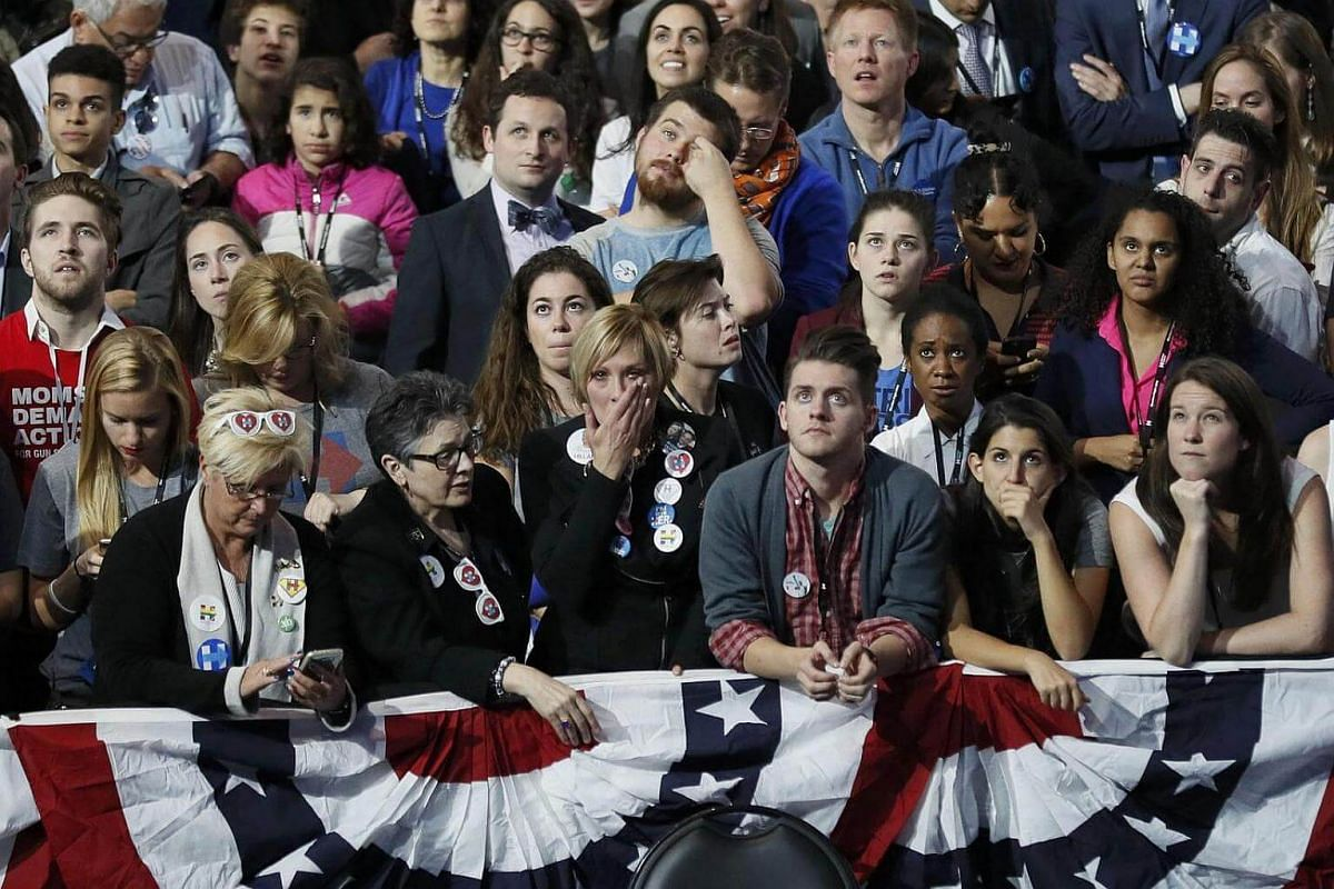 Supporters of Democratic US presidential nominee Hillary Clinton reacting as they watch returns come in at the election night rally in New York on Nov 8, 2016.