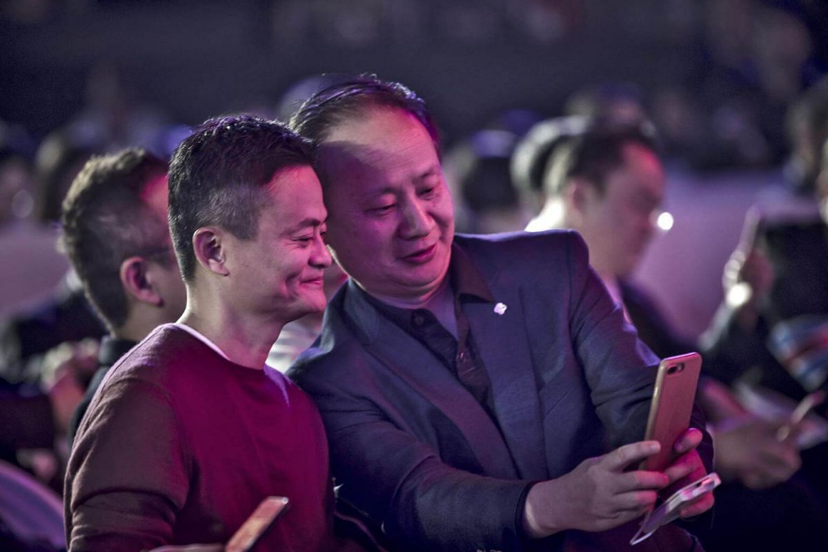 Billionaire Jack Ma (left), chairman of Alibaba Group Holding Ltd., taking a photograph during the Alibaba 11.11 Global Shopping Festival Countdown Gala on Nov 10, 2016.