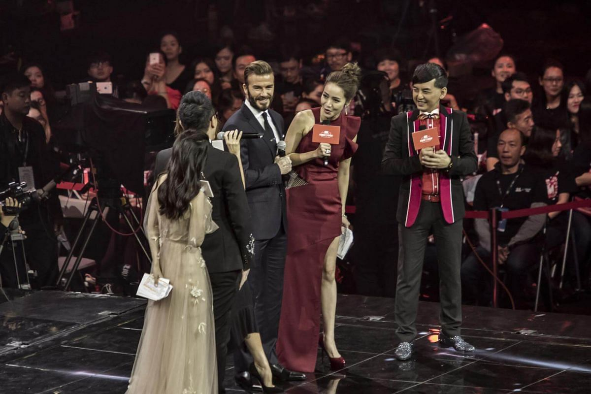 Football celebrity David Beckham (centre) smiles while his wife Victoria Beckham speaks on stage with the hosts of the event during the Alibaba 11.11 Global Shopping Festival Countdown Gala on Nov 10, 2016.