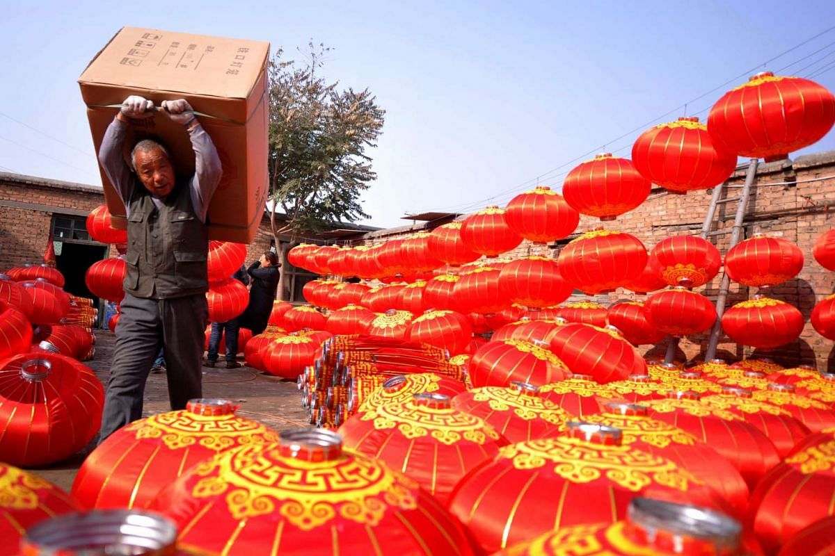 A man carrying a box of lanterns at a lantern workshop in a village in Shijiazhuang, north China's Hebei province on Nov 10, 2016.
