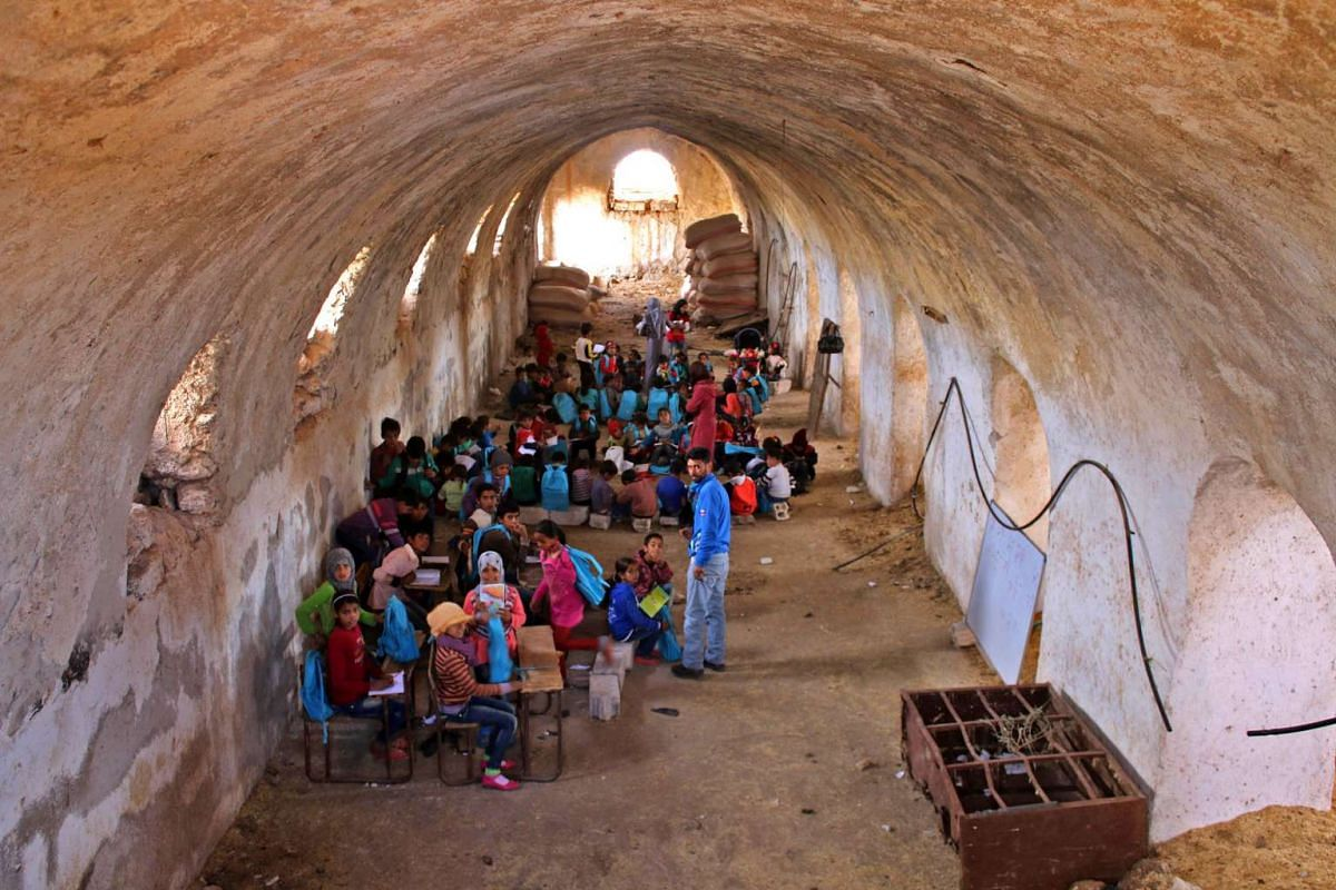 A Syrian teaches children basic arithmetic operations during class in a barn that has been converted into a makeshift school to teach internally displaced children from areas under government control, in a rebel-held area of Daraa, in southern Syria