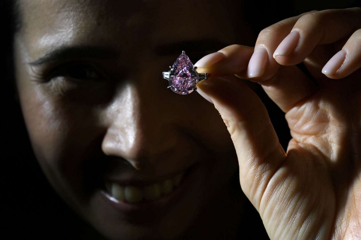 "A model shows ""The Pink"", a fancy vivid pink pear-shaped diamond, during a press preview by Christie's auction house in Geneva on Nov 10, 2016."
