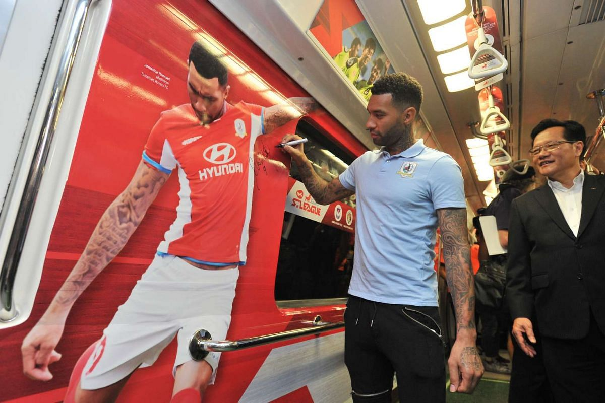 Former Tampines FC star footballler Jermaine Pennant autographing his photo on an SMRT train before it was put straight into service.