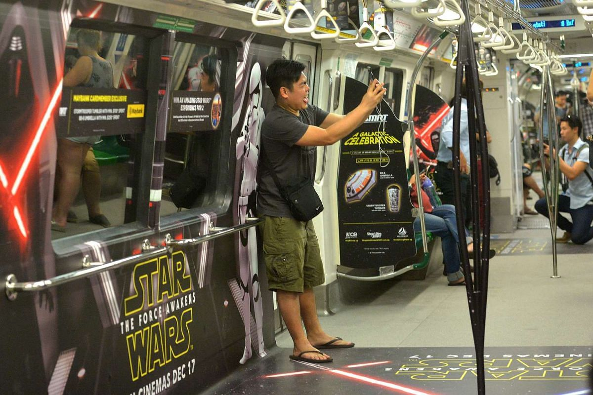 A commuter taking a selfie with the Star Wars poster on board of a Star Wars-themed MRT train. The launch is in line with the world premiere of the latest instalment of the series, Star Wars: The Force Awakens.