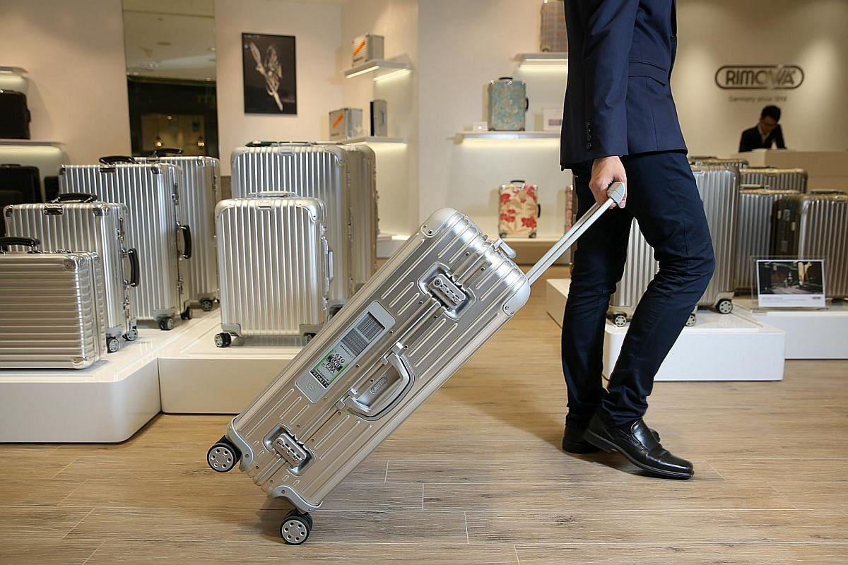 A traveller can check in luggage from home with a Rimowa Electronic Tag bag by keying into a Rimowa app his boarding information (left). The details are reflected on a display panel on the side of the bag.