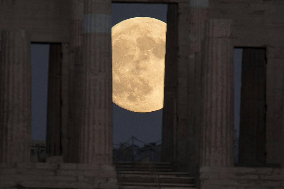 The moon rises and is seen through the ancient Parthenon of the Acropolis in Athens, Greece, on Nov 13, 2016.