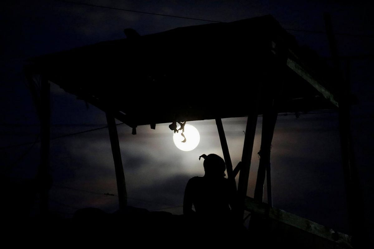 A woman sitting on the rooftop terrace of a house during the 'supermoon' in Port-au-Prince, Haiti, on Nov 13, 2016.
