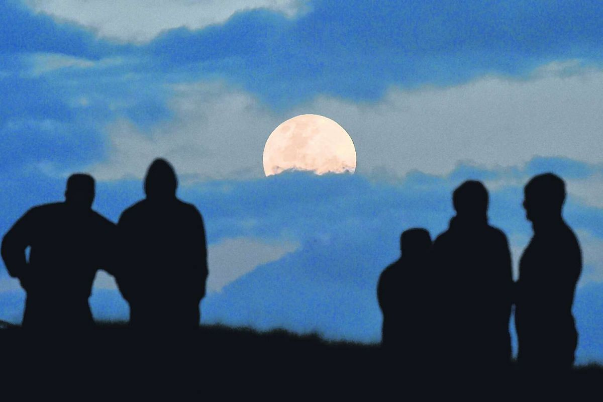 A crowd watches as the full moon is seen between the clouds from Balg Hill south of Sydney on Nov 14, 2016.